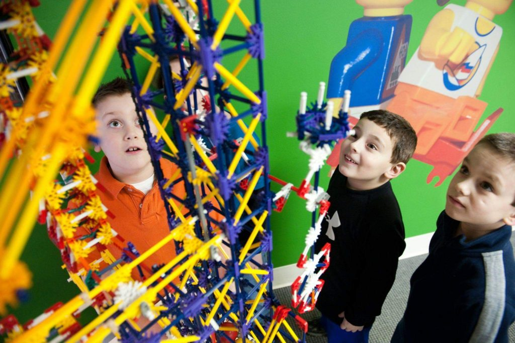 Boys look up at Lego structure.